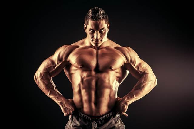 30788906 - handsome muscular bodybuilder posing over black background.
