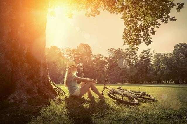 46573937 - woman sitting under sun light at day near her bicycle in the park