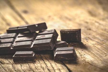 37137467 - noble dark chocolate on a wooden table in vintage style.