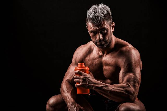 43856263 - tired after training a young man, drinking a protein from banks