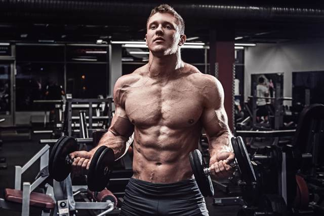 56658716 - muscular man with dumbbells in gym