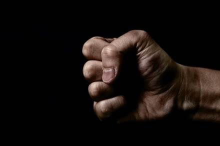12396541 - clenched fist on black background