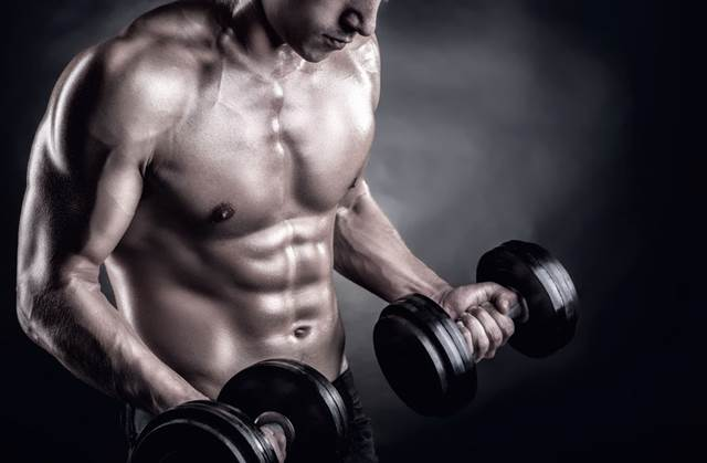 35575894 - closeup of a muscular young man lifting weights on dark background